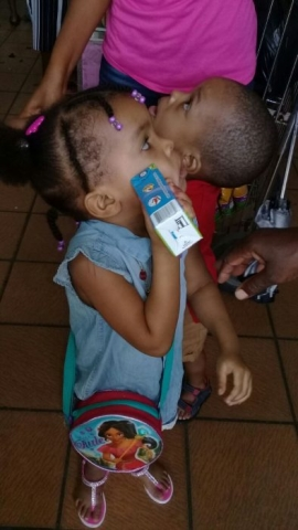 Little girl with Hey Kids It's Juice Time Box on her face