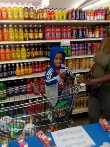 Little Girl in Cart Sampling Juice Time