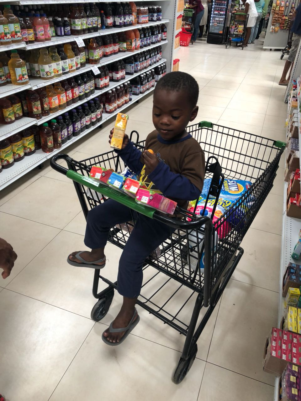 Child in Cart Looking at Juice Time Boxes